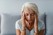 Senior woman having headache and touching her temples. Mature woman sitting on a white sofa in a home touching her head with her hands while having a headache pain and feeling unwell