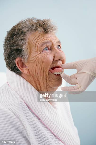 Senior woman having her dentures fitted