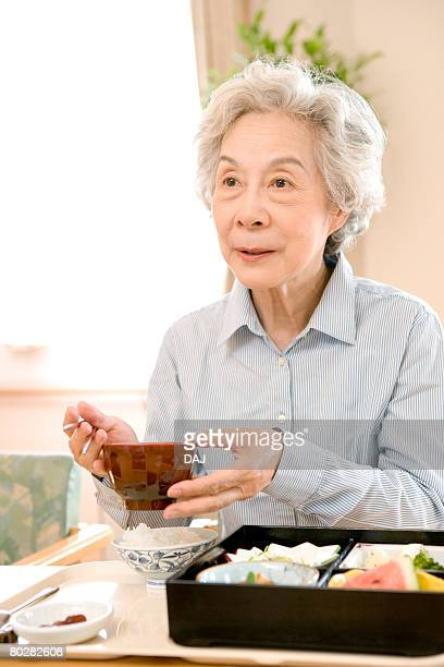 Senior woman having lunch in hospital, holding soup bowl