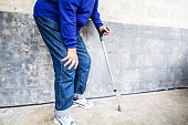 Senior woman standing at a wall with a crutch, having severe knee pain. XXXL size image. 50Mpx. iStockalypse, Paris, 2016.