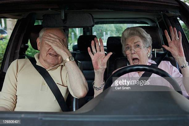 Senior woman having trouble learning to drive as man in passenger seat despairs