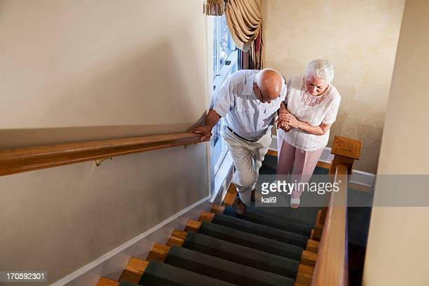 Senior woman helping husband climb staircase