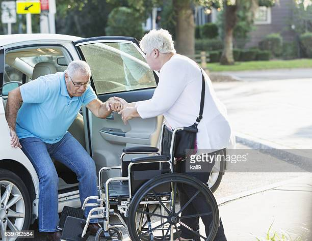 Senior woman helping husband from car to wheelchair