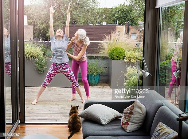 senior woman helps daughter with  yoga stretch