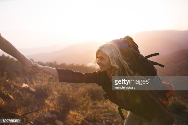 Senior woman hiker getting a helping hand to climb mountain