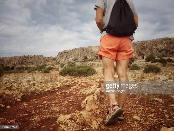 Senior woman hiking alone on dirt road, Sicily