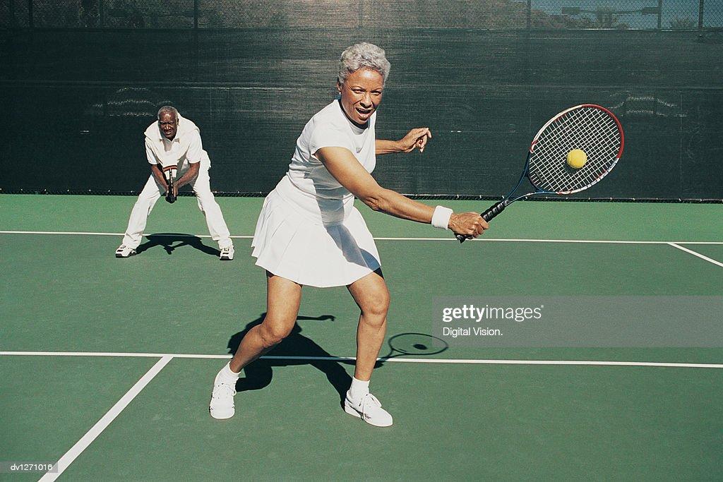 Senior Woman Hitting a Tennis Ball on a Tennis Court and a Senior Man Standing Behind : Stock Photo
