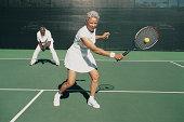 Senior Woman Hitting a Tennis Ball on a Tennis Court and a Senior Man Standing Behind