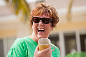 Senior woman holding a cup and laughing