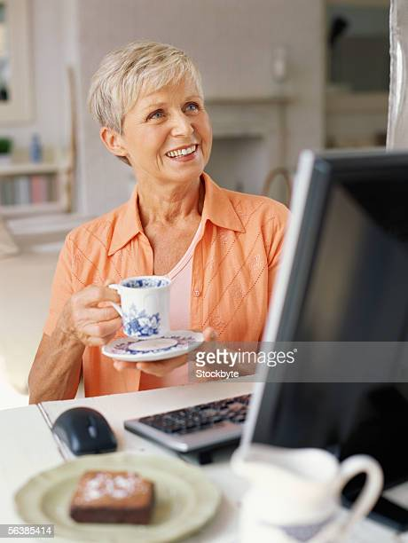 senior woman holding a cup and saucer in front of a computer