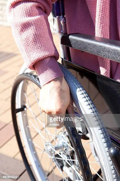 Senior woman holding a rim of wheelchair
