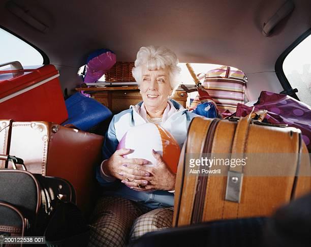 Senior  woman holding beach ball in car full of luggage