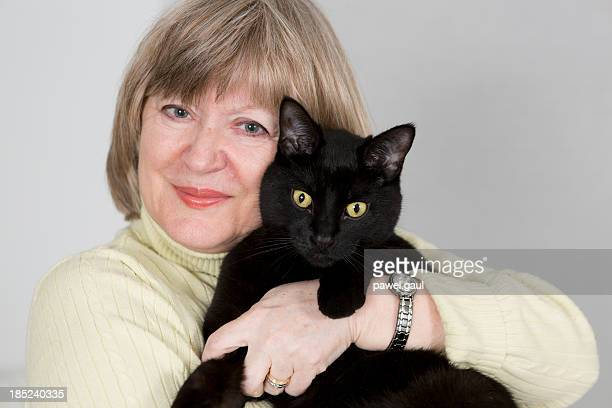 Senior woman holding black cat