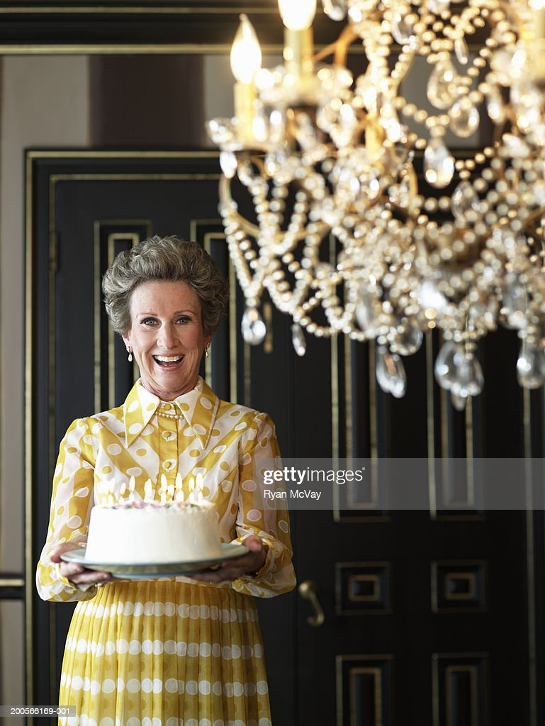 Senior woman holding cake lit with candles, smiling, portrait : Stock Photo