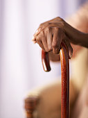 Senior woman holding cane, close-up of hands
