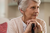 Serious senior woman sitting on couch holding walking stick and looking away. Portrait of thoughtful old grandmother leaning on cane. Elderly sad lady with her walking stick.