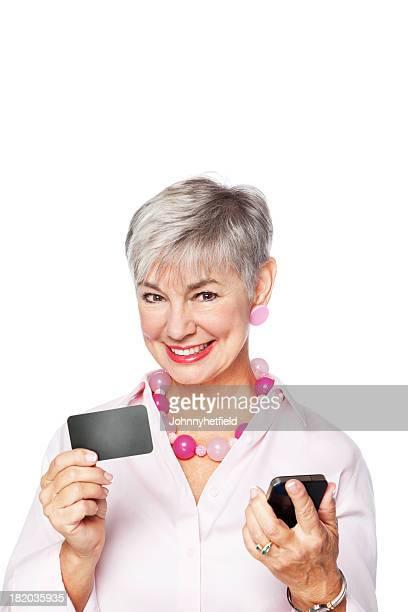 Senior mujer sosteniendo el teléfono móvil con tarjeta de crédito en