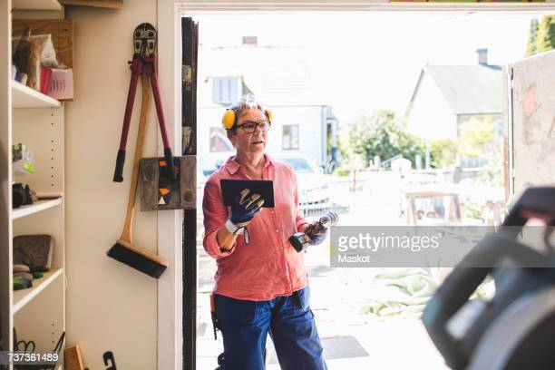 Senior woman holding drill and digital tablet while standing at doorway of workshop
