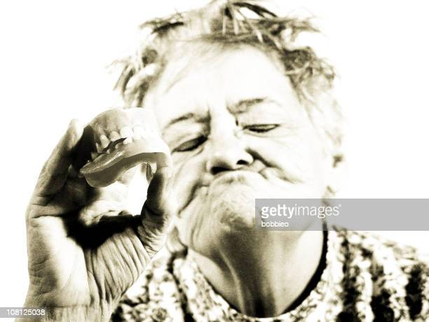 Senior Woman Holding False Teeth Out, Sepia Toned