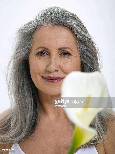 Senior woman holding flower, close-up, portrait