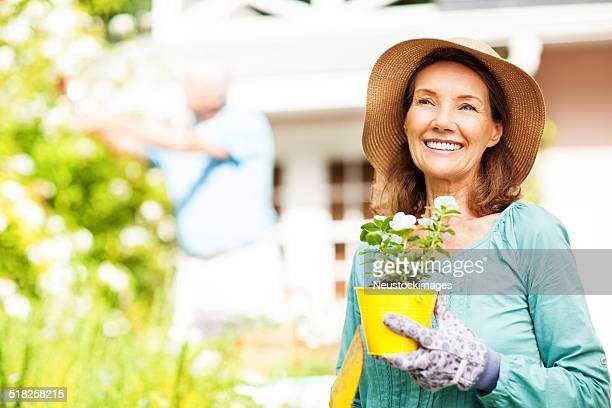 Senior Frau hält Blumentopf während Man Gardening In den Garten