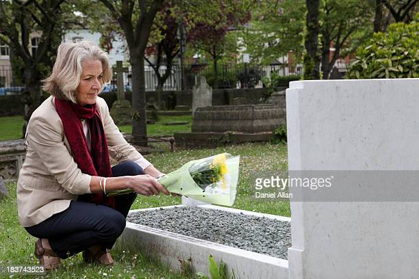 Senior woman holding flowers at grave stone