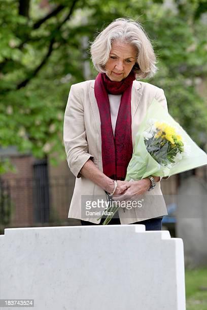 Senior woman holding flowers in graveyard