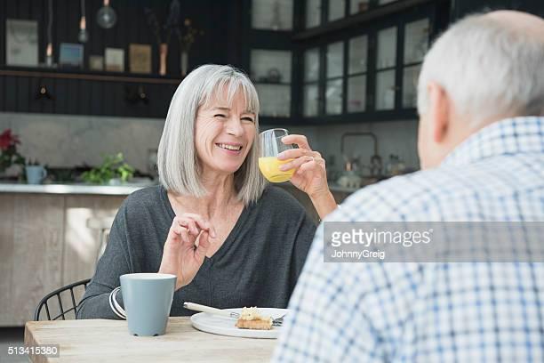 Senior Frau hält frischen Orangensaft beim Frühstück, Lächeln