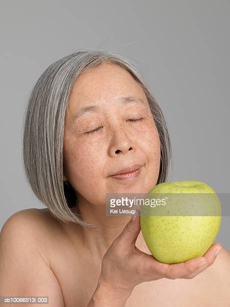Senior woman holding green apple, close-up
