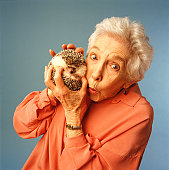 Senior woman holding hedgehog, (Portrait)