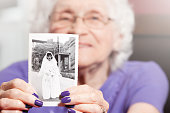 An 89 year old woman holding a photo of herself as a young bride.