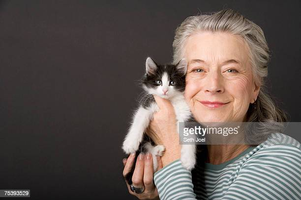 Senior woman holding kitten in studio, portrait