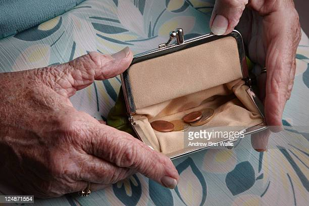 Senior woman holding open a purse on her lap
