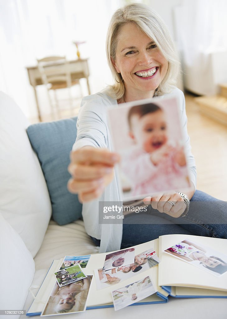 Senior woman holding photo of baby : Stock Photo