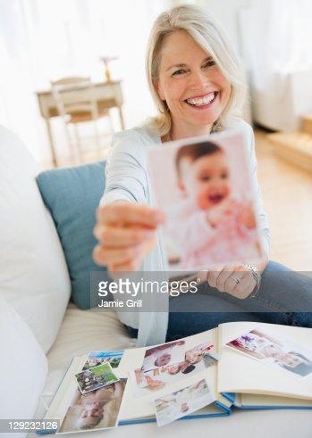 Senior woman holding photo of baby : Stock Photo