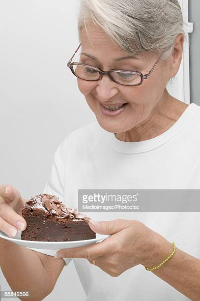 Senior woman holding piece of chocolate cake on plate