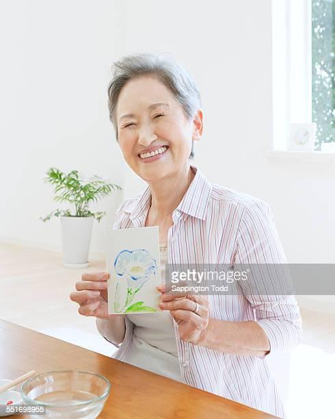Senior Woman Holding Postcard