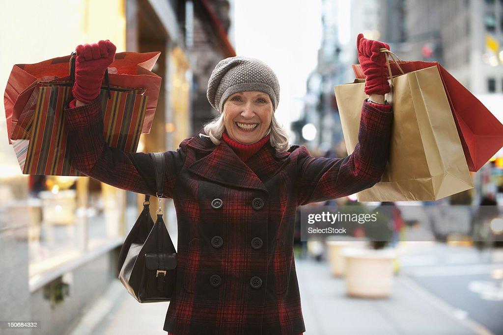 Senior woman holding shopping bags : Stock Photo