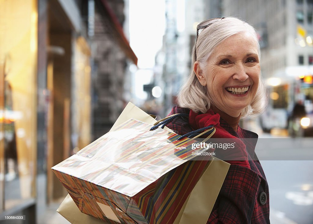Senior woman holding shopping bags : Stock Photo