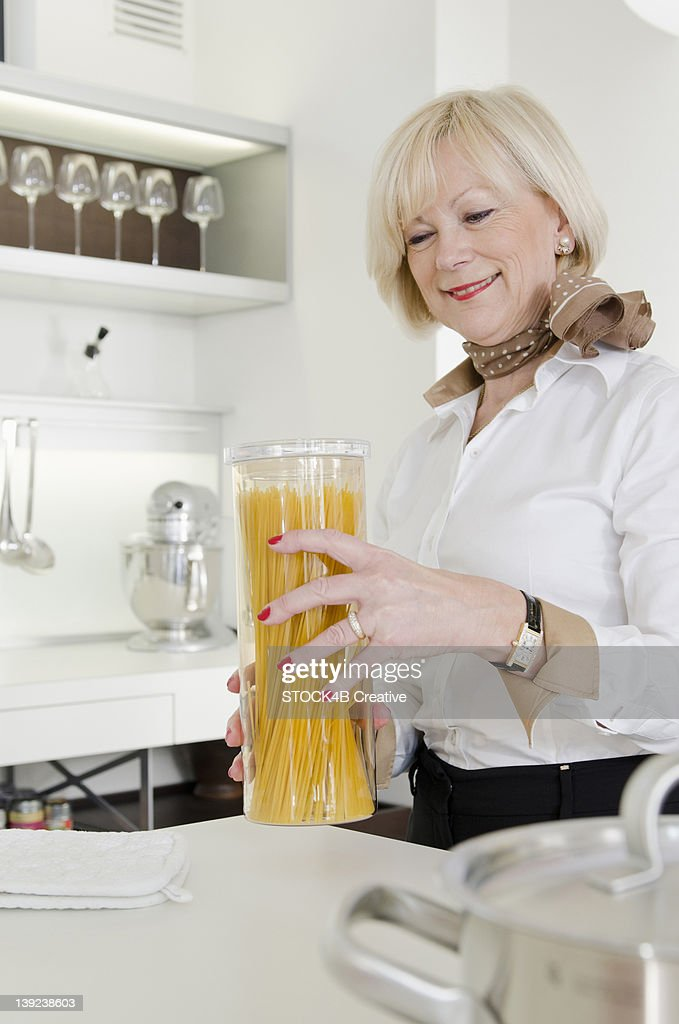 Senior woman holding Spaghetti glass in kitchen : Stock Photo
