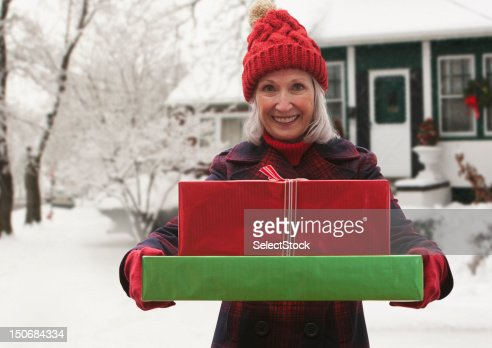 Senior woman holding stack of presents : Stock Photo