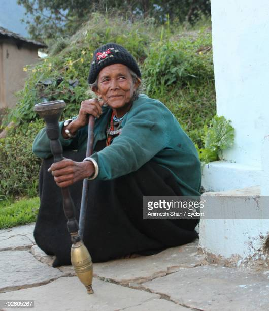 Senior Woman Holding Tobacco Pipe While Crouching By Wall