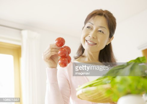 Senior Woman Holding Tomatoes Stock Photo Getty Images