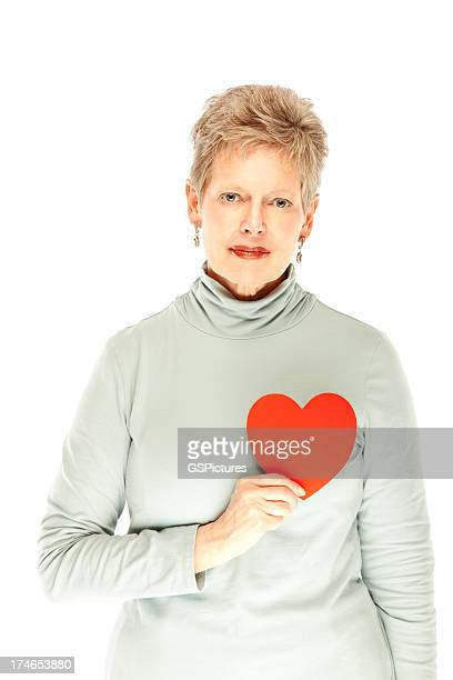 Senior Woman Holding up a Red Heart. Isolated.
