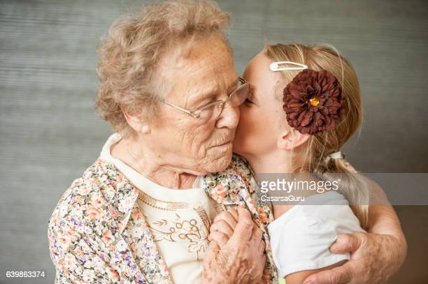 Senior Woman Hugging a Little Girl
