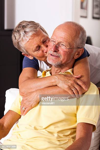 Senior woman hugging and kissing her husband