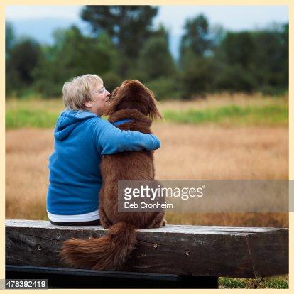 Senior woman hugging brown dog on bench