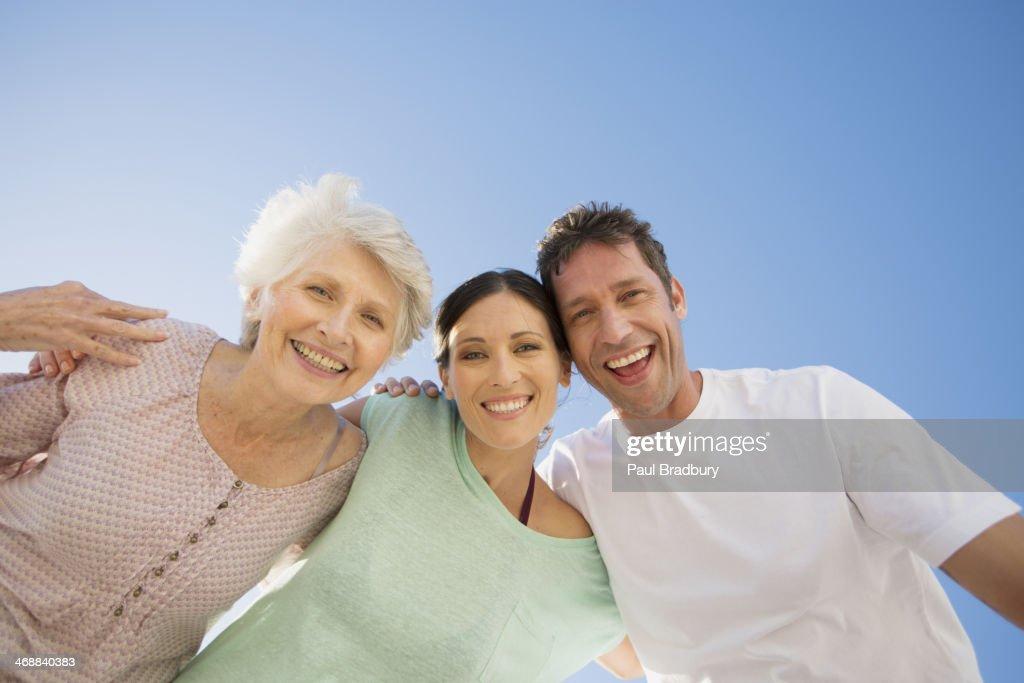 Senior woman hugging couple against blue sky