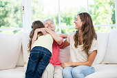Senior woman hugging granddaughter while sitting on sofa at home
