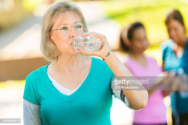 Senior woman hydrates after exercising
